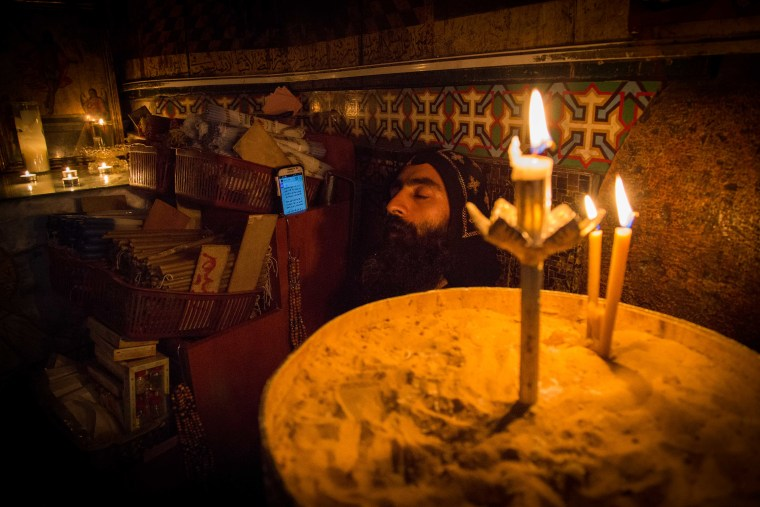 Image: An Egyptian Coptic Christian rests inside a small room attached to the Edicule of the Tomb, as construction work begins on the Church of the HolySepulchre in Jerusalem