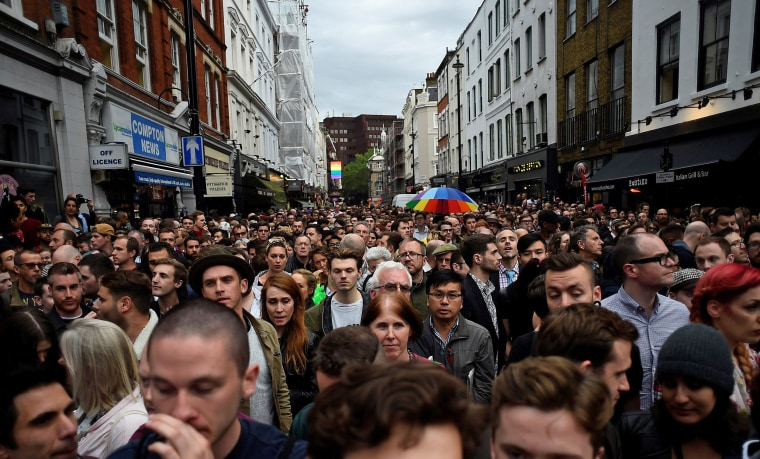 Image: People pause during a minute's silence in memory of the victims of the gay nightclub mass shooting in Orlando, in the Soho district of London