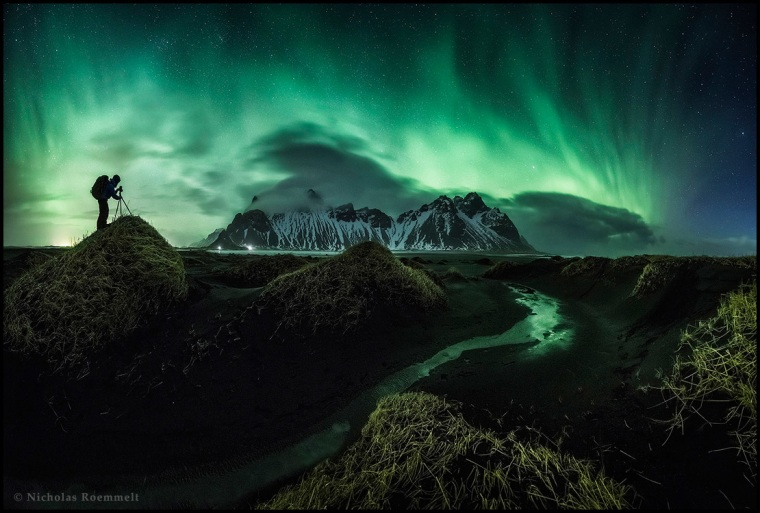 """""""The Photographer"""" by Nicholas Roemmelt from Austria is the second place winner in the Beauty category, taken in March 2015 in Stockiness, Iceland.   """"It was not easy for my buddy Nikki Haselwanter to literally """"freeze"""" for 15 seconds for the shot on the top of that sand dune with wind gusts of 25m/s. Blizzards kept on hitting the coastline that night and it had been challenging not to been blown away. But during clear gaps of few minutes we could witness the wonderful northern lights behind the Icelandic Vestrahorn."""""""