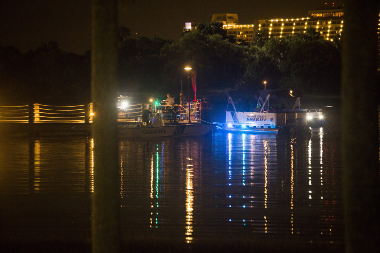 Image: Police officers search for a child who was reportedly being pulled into the water by an alligator