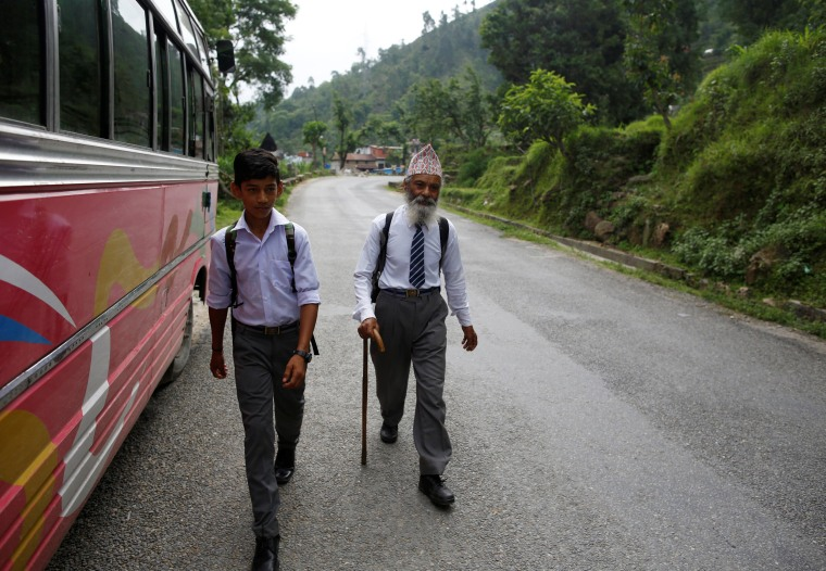 Image: Sagar Thapa, 14, walks with Kami as they head to school.