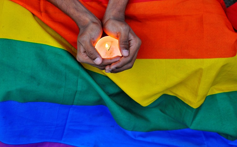 Image: A member of the LGBT community in Bengalaru holds a candle during a memorial service following a mass shooting at the Pulse gay nightclub in Orlando