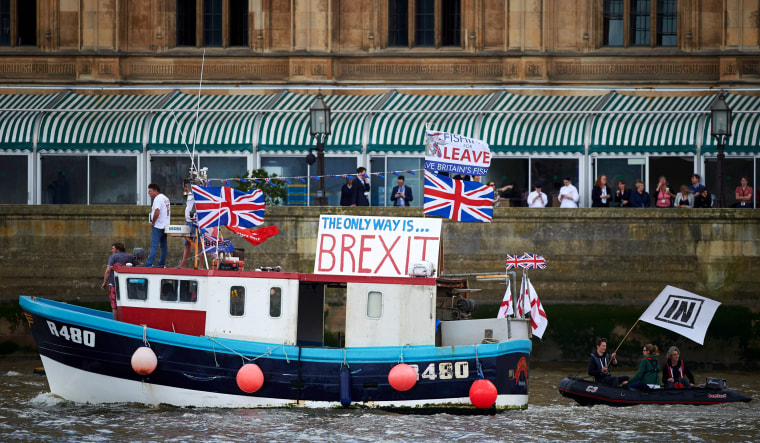 Image: A boat decorated with flags and banners from the 'Fishing for Leave' group