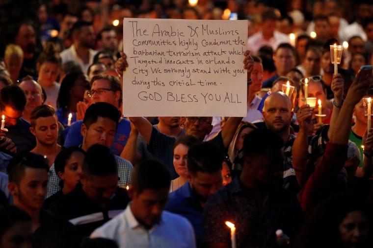 Image: A man holds up a sign saying Arab Muslims condemn the attack as he takes part in a candlelight memorial service the day after a mass shooting at the Pulse gay nightclub in Orlando
