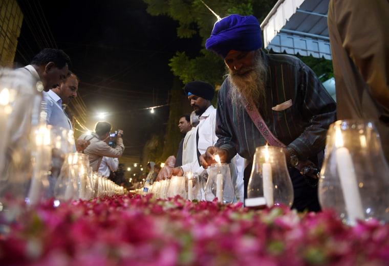 Image: Pakistani supporters of Muttahida Qaumi Movement (MQM) light candles in Karachi