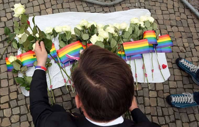 A visitor places flowers at a makeshift memorial during a vigil for victims of a shooting at a gay nightclub in Orlando, Florida the previous day, in front of the United States embassy on June 13, 2016 in Berlin, Germany.