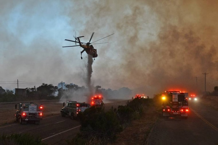 Image: A sky crane helicopter makes a drop as the Sherpa Fire burns