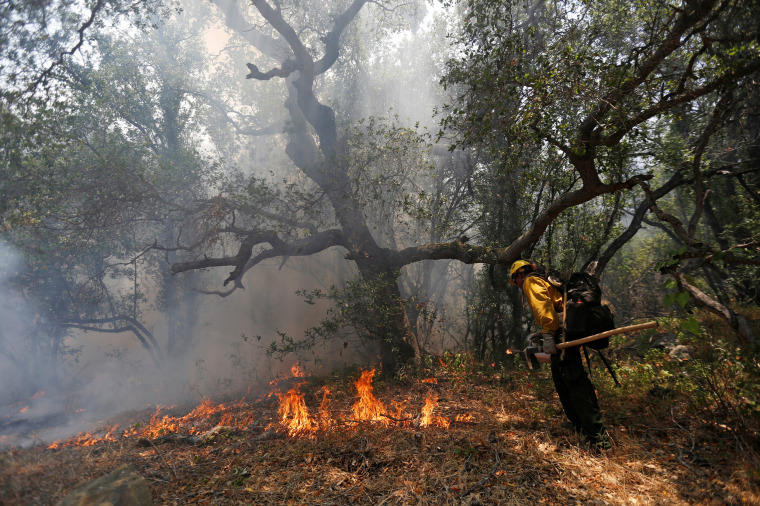 "Image: A Hotshots member from the U.S. Forest Department sets a back fire while battling the the so-called ""Sherpa Fire"", which has grown to over 1100 acres overnight, in the hills near Goleta"
