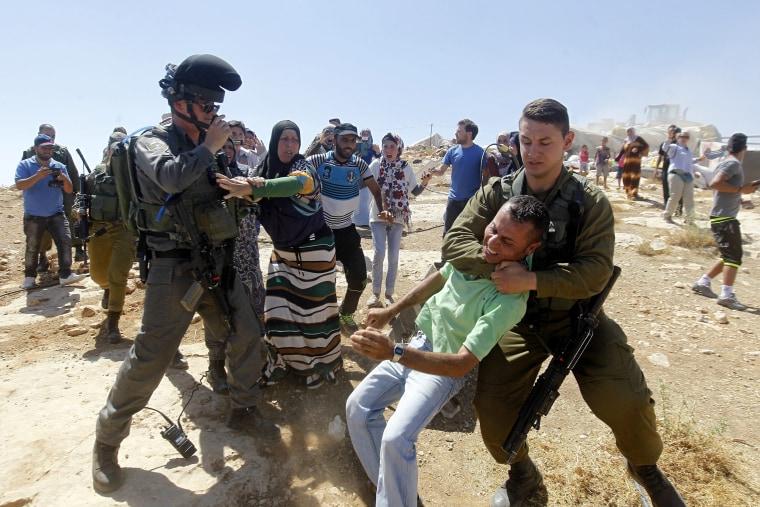 Image: Israeli soldiers demolish Palestinian houses in military zone