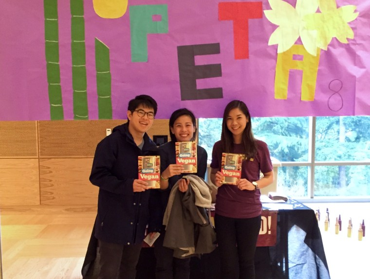 Victoria Hong, right, passing out vegan cookbooks at a college cultural event.