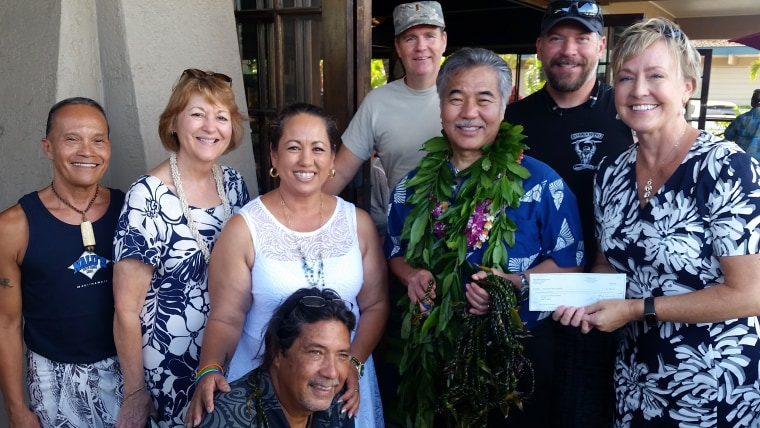 Maui's lei of aloha for Orlando, made by volunteers with ti leaves over four days in Maui, Hawaii. From left: Kawika Sabado, lei making instructor; Hawaii state Sen. Roz Baker; Stacey Moniz; Patrick Mulligan; Gov. David Ige; Lisa Paulson from Maui Hotel and Lodging Association. Front: Ron Panzo, owner of Nalu's South Shore Grill.