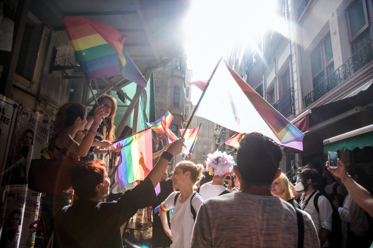 People wawe rainbow flags as Turkish anti-riot police officers fire rubber bullets to disperse demonstrators gathered for a rally staged by the LGBT community on Istiklal avenue in Istanbul on June 19, 2016.