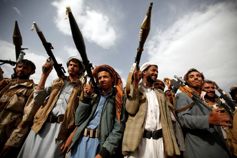 Image: Houthi fighters carry their weapons as they attend a tribal gathering in Sanaa