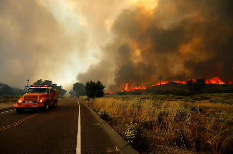 Image: Firefighters move to try and head off a fast moving wildfire as it burns near Potero, California