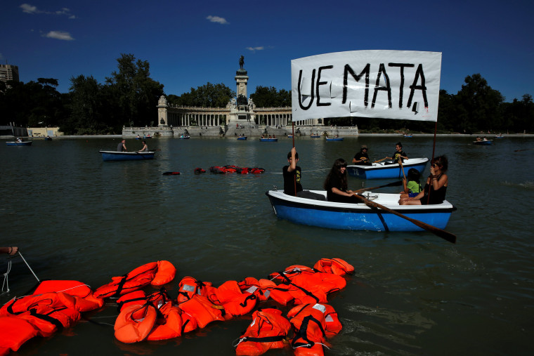 """Image: Activists hold a banner that reads """"European Union kills"""" in a boat next to floating life jackets as people row rental boats during a protest to mark World Refugee Day at Retiro park in Madrid"""