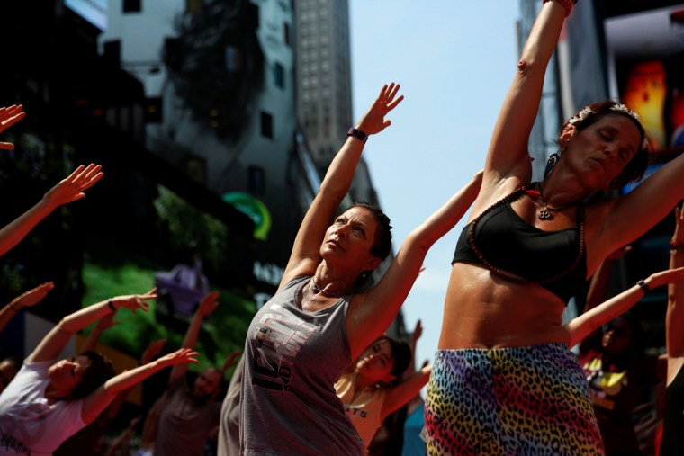 Image: People participate in a yoga class during the 14th Annual Solstice in Times Square event in New York