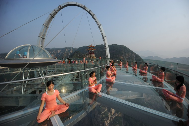 Image: People practise yoga at a glass sightseeing platform ahead of the International Day of Yoga, on the outskirts of Beijing