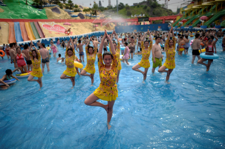 Image: Yoga lovers guide tourists to practise yoga at a water park to cool off in Chongqing