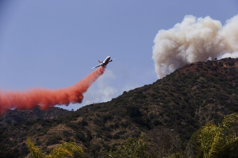 Image: A firefighting plane makes a retardant drop on a hill near a Azusa wildfire in Azusa, Calif.
