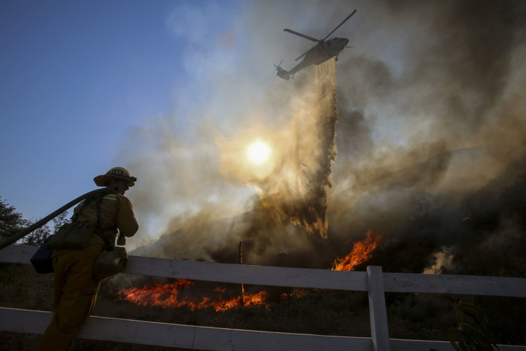 Image: A firefighter watches as a helicopter making a drop on a wildfire in Azusa, Calif
