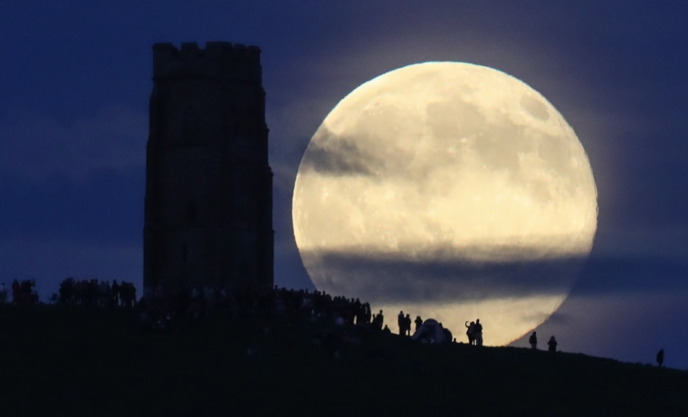 Image: A full moon rises behind Glastonbury Tor as people gather to celebrate the summer solstice