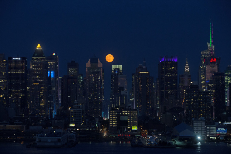 Image: The moon rises above skyscrapers in Manhattan, New York