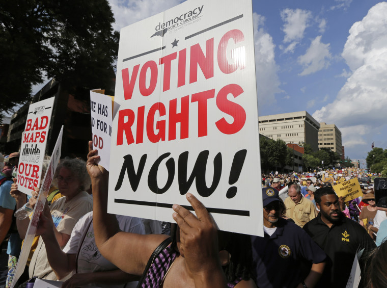 Image: A woman holds a voting rights sign as demonstrators march through the streets of Winston-Salem, N.C.