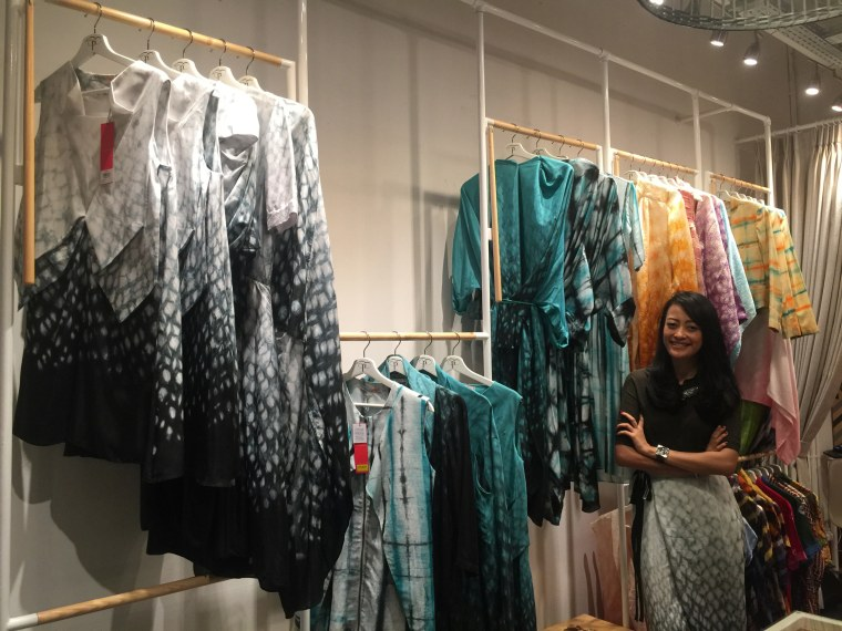 Nonita Respati in her Kemang, Jakarta, Indonesia, PURANA storefront next to some of her batik fabric-based designs.