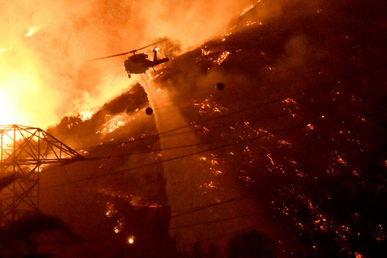 Image: A Los Angeles County fire helicopter makes a night drop while battling the so-called Fish Fire above Azusa, California