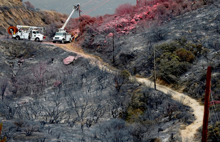 Image: Utility workers begin work repairing power and data lines after a wildfire near Potrero