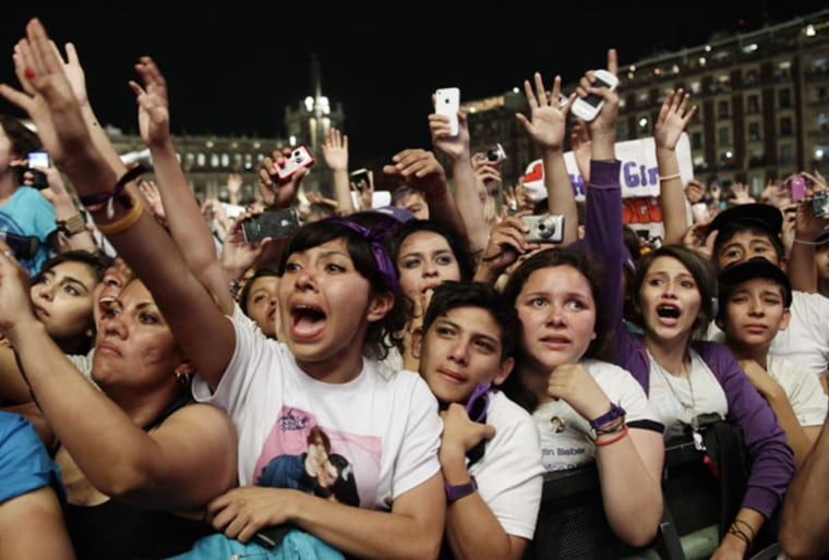 Fans of Canadian pop singer Justin Bieber react as he performs at a free open-air concert at Zocalo Square in Mexico City