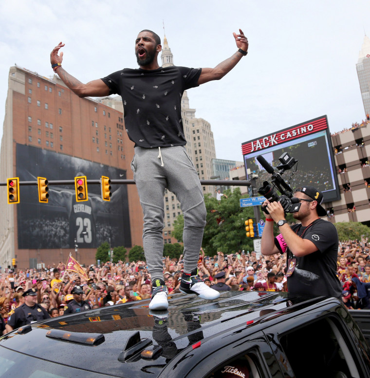 Image: Cleveland Cavaliers Kyrie Irving celebrates with the crowd in downtown Cleveland