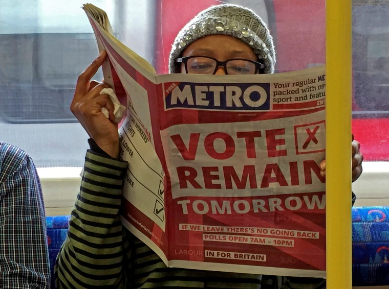 Image: A woman reads a newspaper on the underground in London with a 'vote remain' advert for the BREXIT referendum