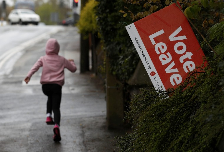 Image: A girl runs past a Vote Leave sign, protruding from the garden of a house in Altrincham