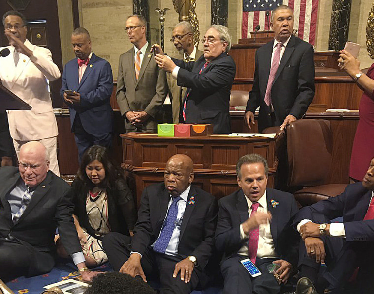 """Rep. John Lewis, bottom center, stages a dramatic sit-in on the House floor with his fellow Democrats to force a vote on gun control. He and roughly 40 fellow House Democrats vowed """"to occupy the floor of the House until there is action."""""""