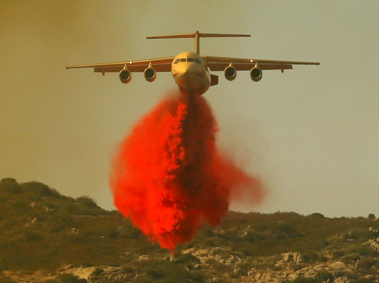Image: A water bomber makes a drop on a wildfire as it attacks the flames near Campo, California