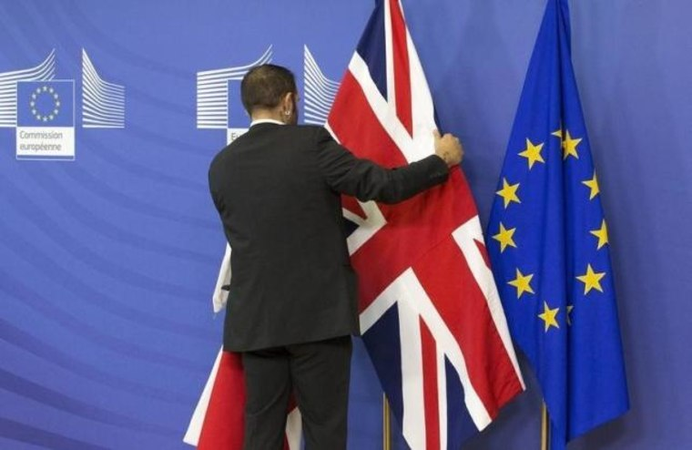 An employee at the European Commission adjusts a British flag ahead of the meeting between Prime Minister Cameron and European Commission President Juncker in Brussels