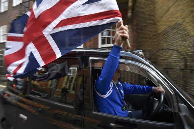 Image: A taxi driver holds a Union flag, as he celebrates following the result of the EU referendum, in central London