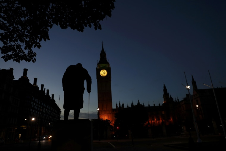 Image: Dawn breaks behind the Houses of Parliament and the statue of Winston Churchill in Westminster, London, Britain