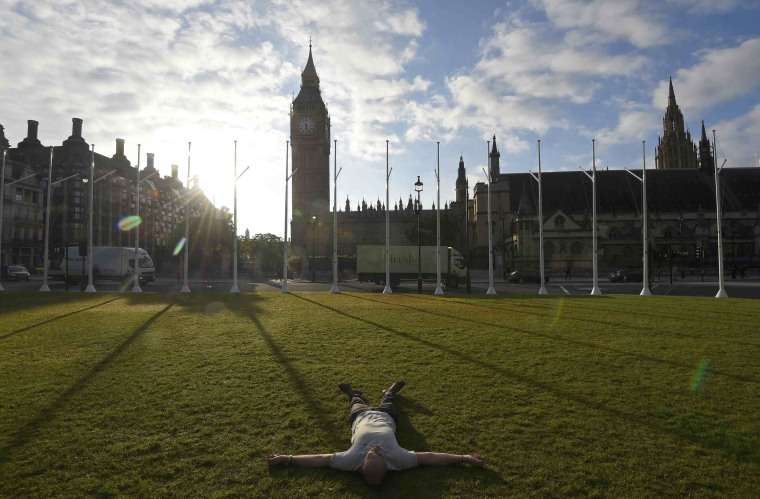 Image: A man lies on the ground in Parliament Square in London