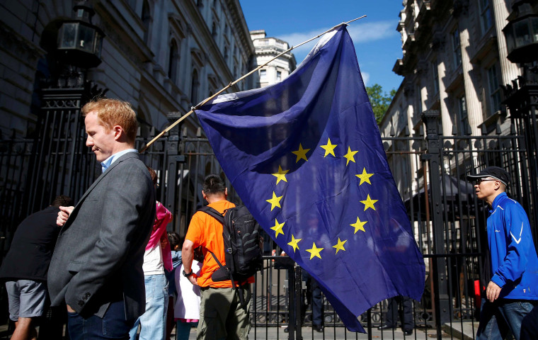 Image: A man carries a EU flag, after Britain voted to leave the European Union, outside Downing Street in London
