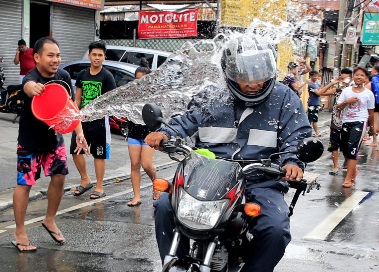 Image: A man throws a bucket of water at a motorcyclist as residents join in a water-splashing frenzy to honor their patron St. John the Baptist's Feast Day in San Juan