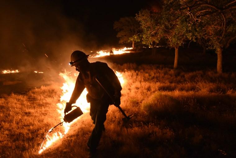 A firefighter sets a backfire by a blaze near Lake Isabella, Calif. on June 24.