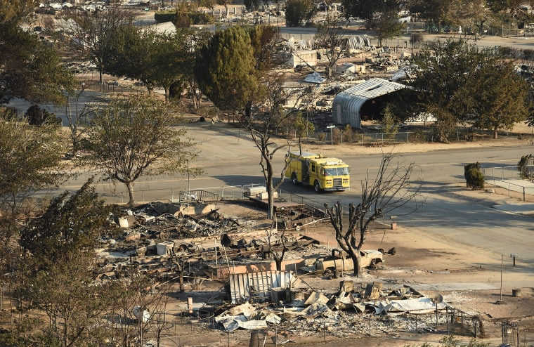 Image: A firetruck drives through a neighborhood decimated by the Erskine Fire in South Lake