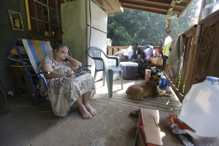 Image: Phyllis Rucker watches recovery efforts from a front porch after flooding in Falling Rock