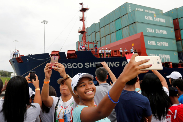 Image: A woman takes a selfie as Chinese COSCO container vessel named Andronikos navigates through the Agua Clara locks during the first ceremonial pass through the newly expanded Panama Canal in Agua Clara