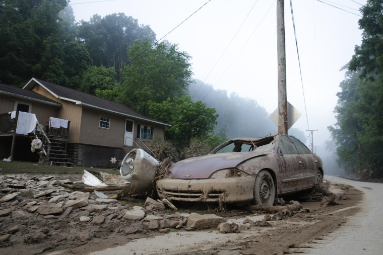 Image: A destroyed car rests in front of a house after flooding in Clendenin