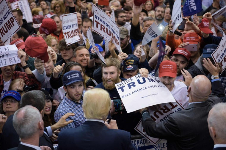Image: Donald Trump signs autographs during a rally in Cleveland