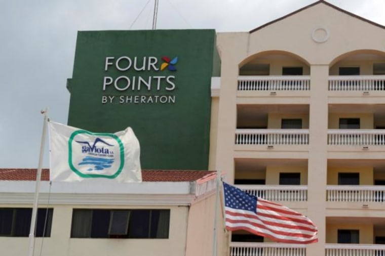 "A U.S. flag and a flag of the Cuban military-run hospitality company Gaviota flutter near the logo of a  ""Four Points by Sheraton"" hotel in Havana"