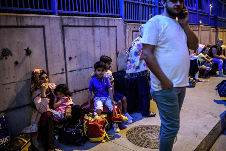Image: People wait with their luggage outside the Ataturk airport in Istanbul